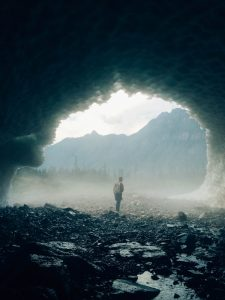 man walking through cave in forest