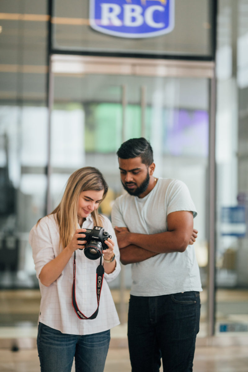 male and female photographers camera sharing