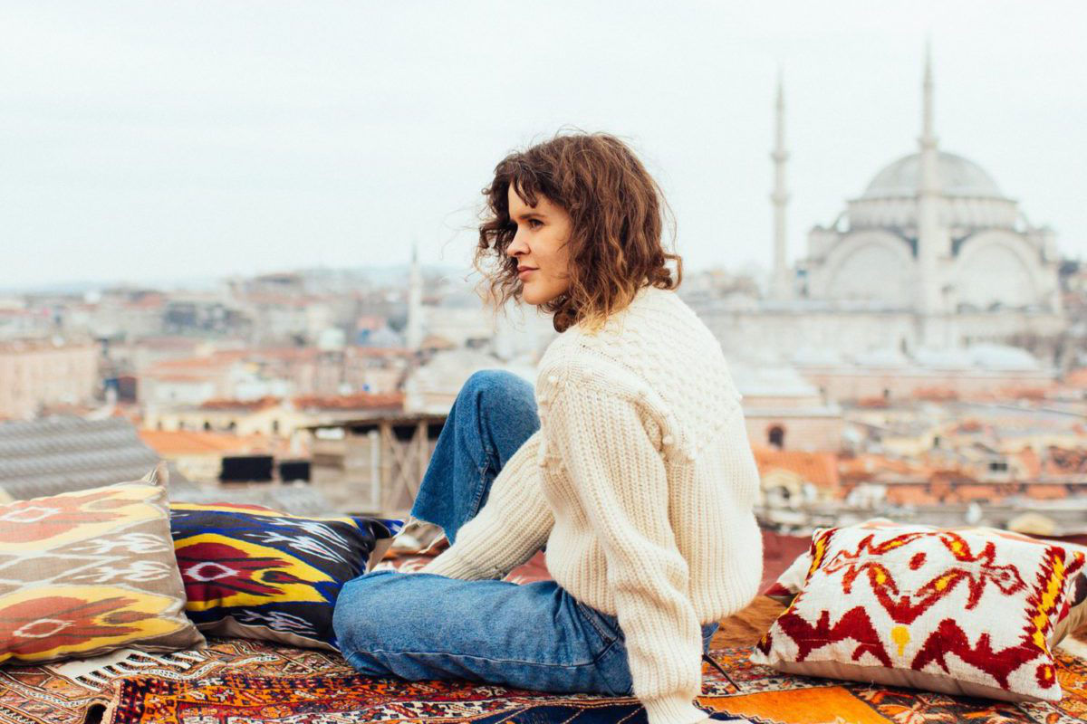 female sitting on colorful rug