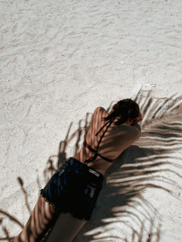 female lying facedown on the beach