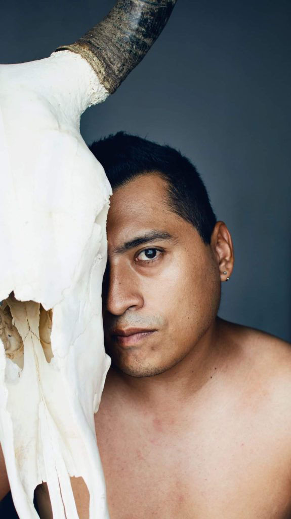 man posing with an animal skull