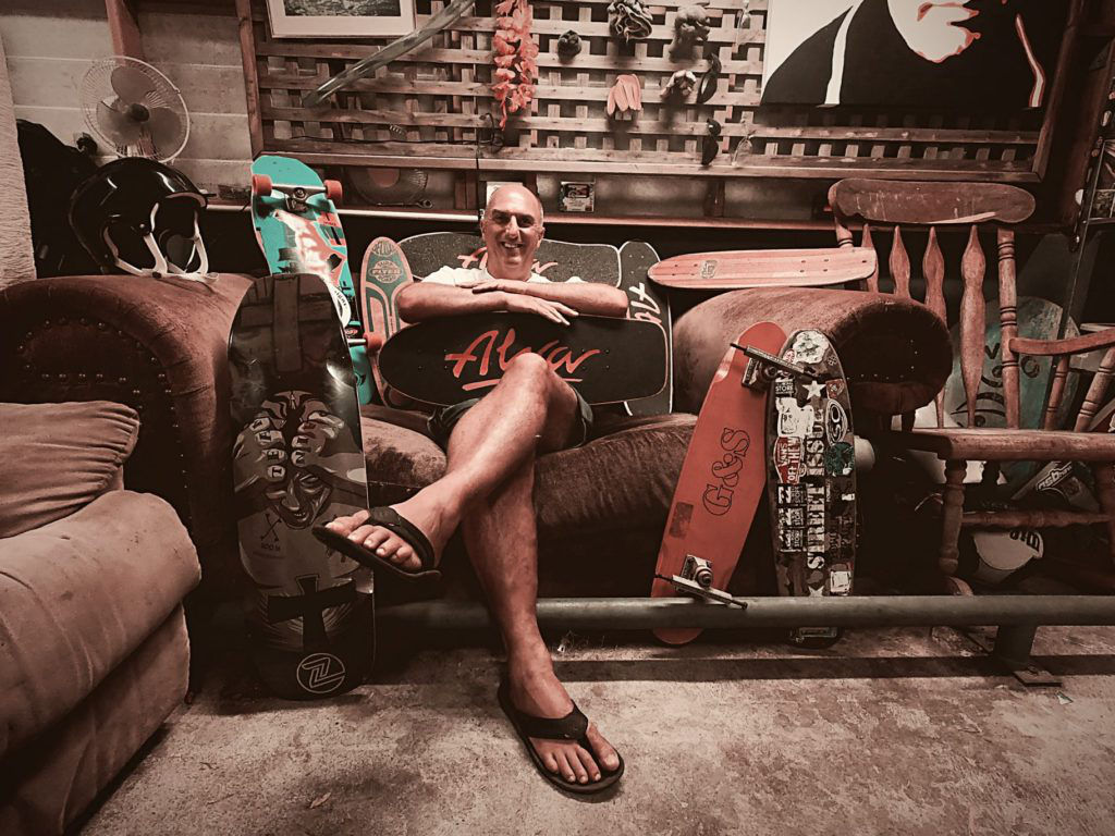 man sitting on the couch with his skateboards