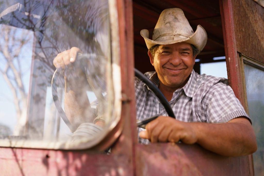 Portrait Happy Man Farmer Driving Tractor Looking At Camera