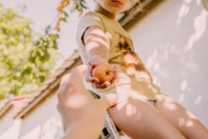 girl holding an apple with a yellow shirt on a ladder