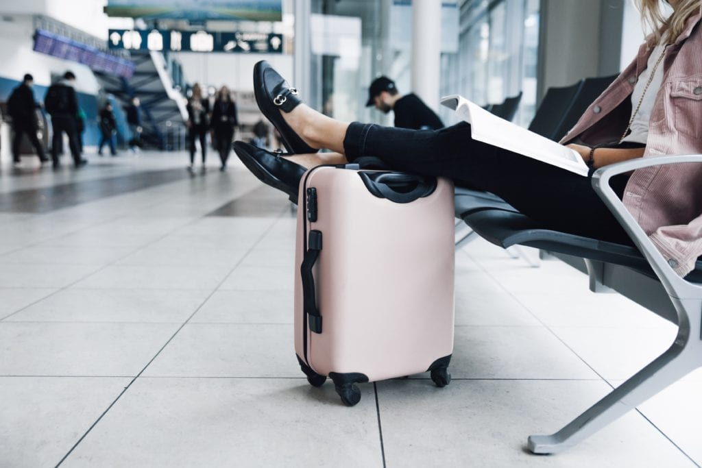 female traveler with feet on suitcase