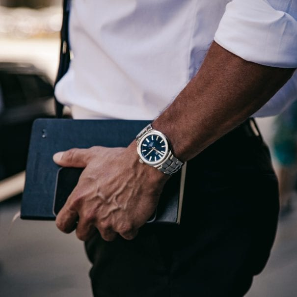 tag heuer watch on man holding book