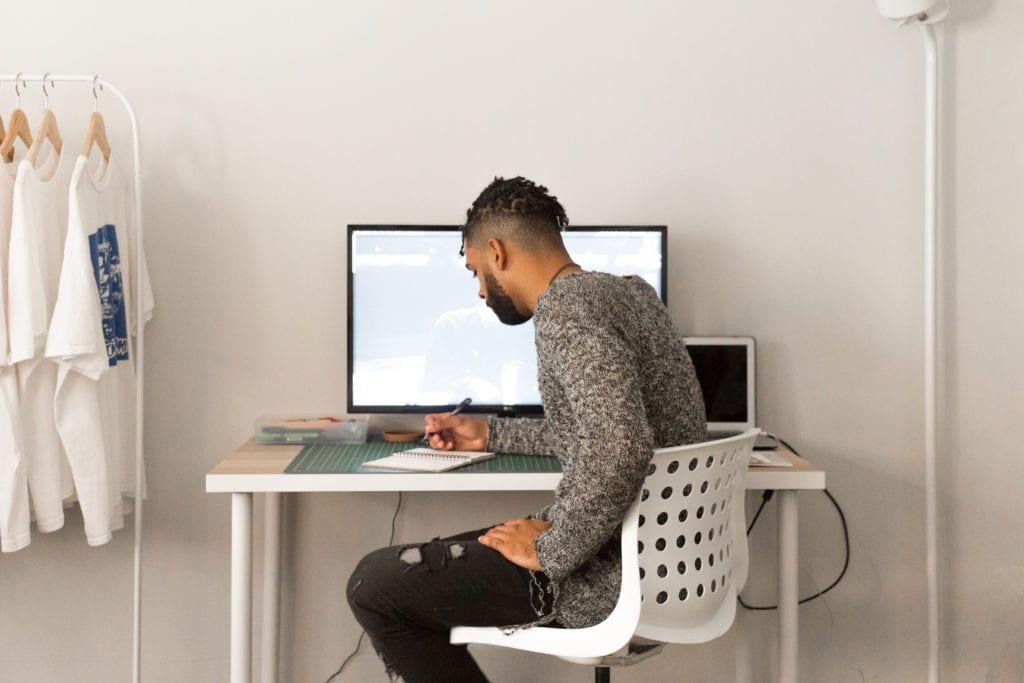 man sitting at desk writing
