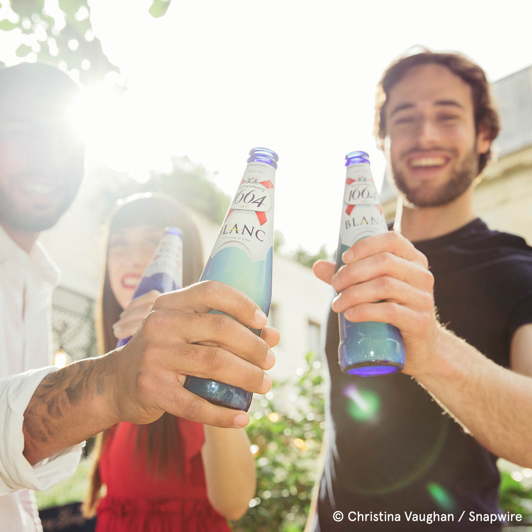 two people cheers bottles with the sun behind them