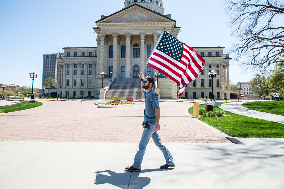 man holding a flag walking in front a government building