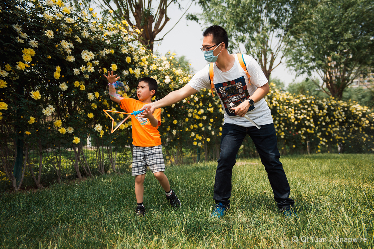 man and kid playing with bubbles in grass