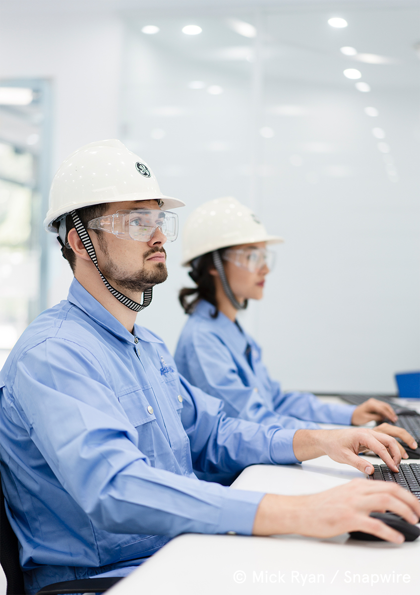 two people in work helmets