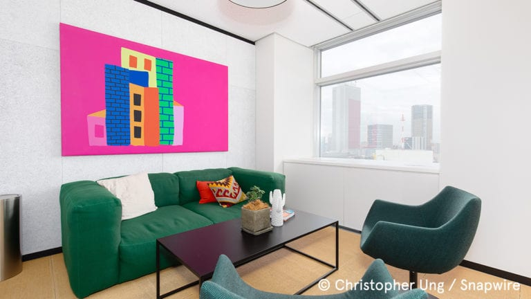 meeting room with green chairs, green sofa, and pink wall art
