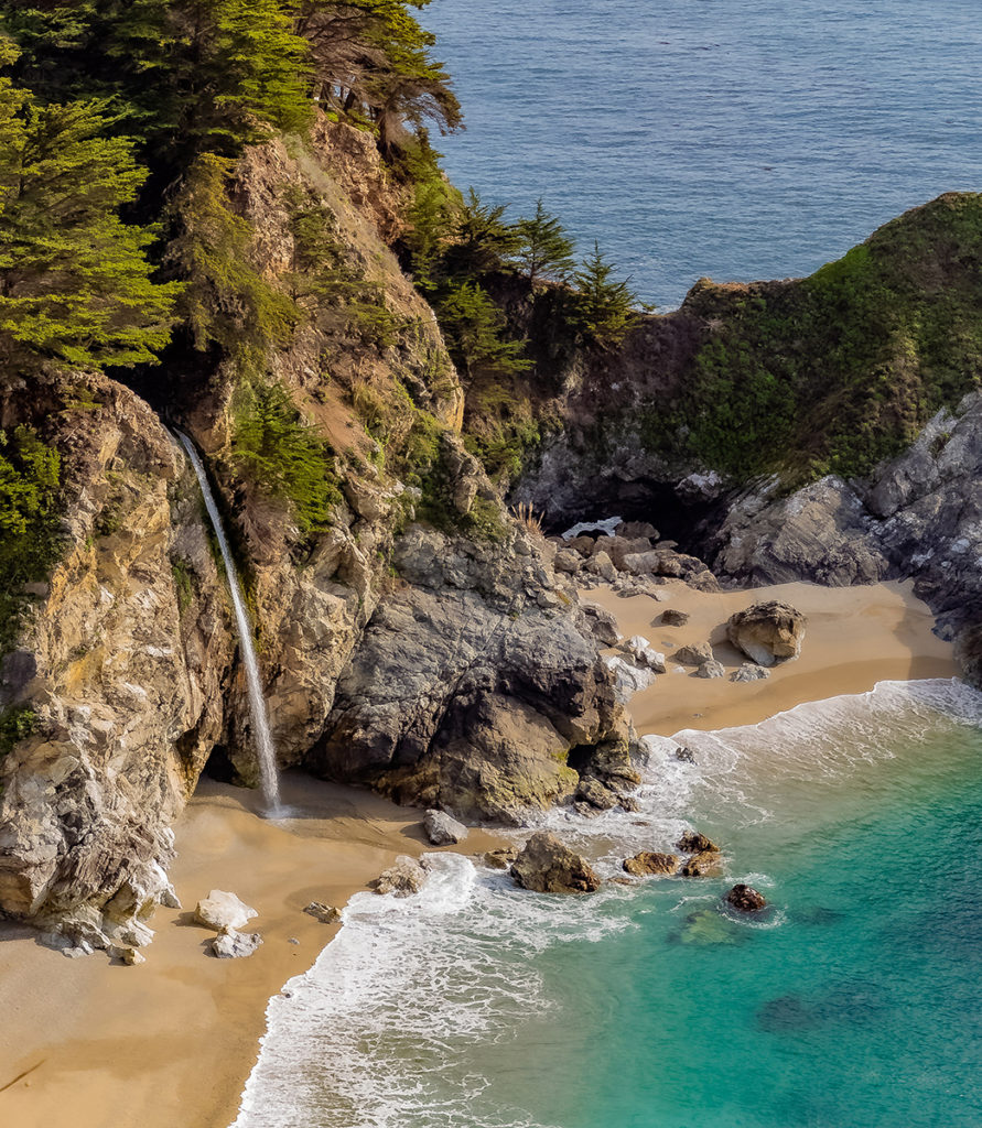 birds eye shot of a cove with a waterfall going into the ocean