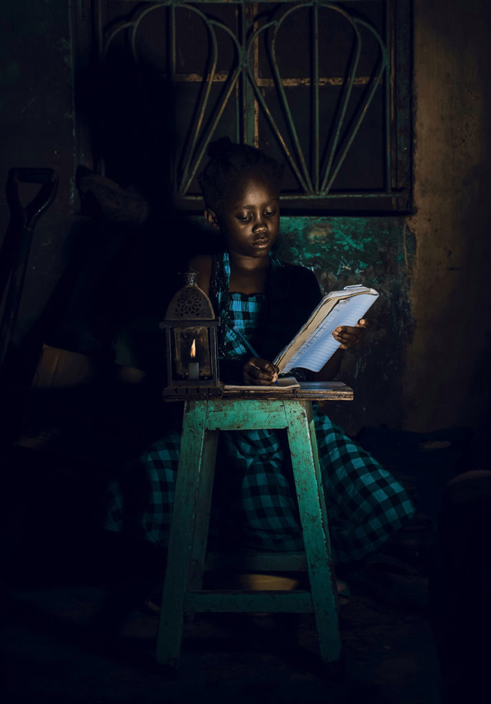 girl writing in a book on a stool