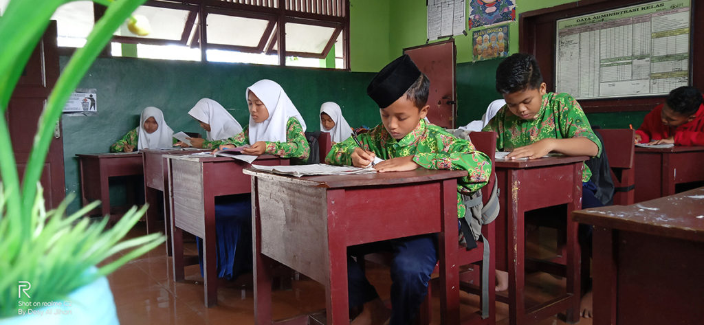 kids sitting down at desks writing