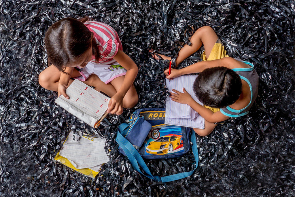 two kids writing in a book on a carpet