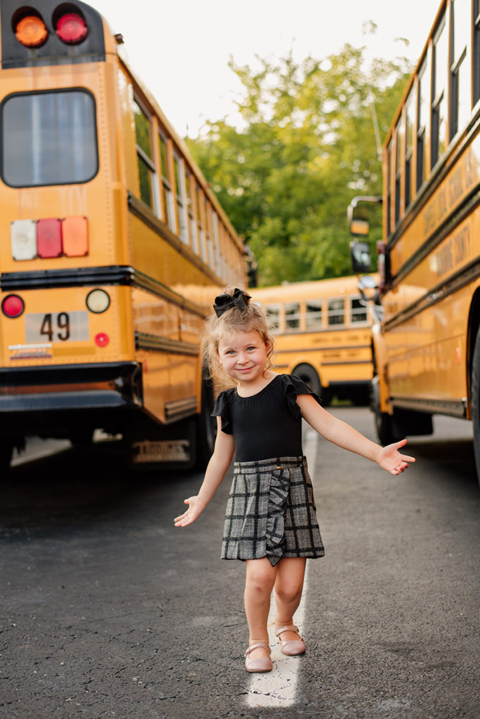 girl walking in between two school buses
