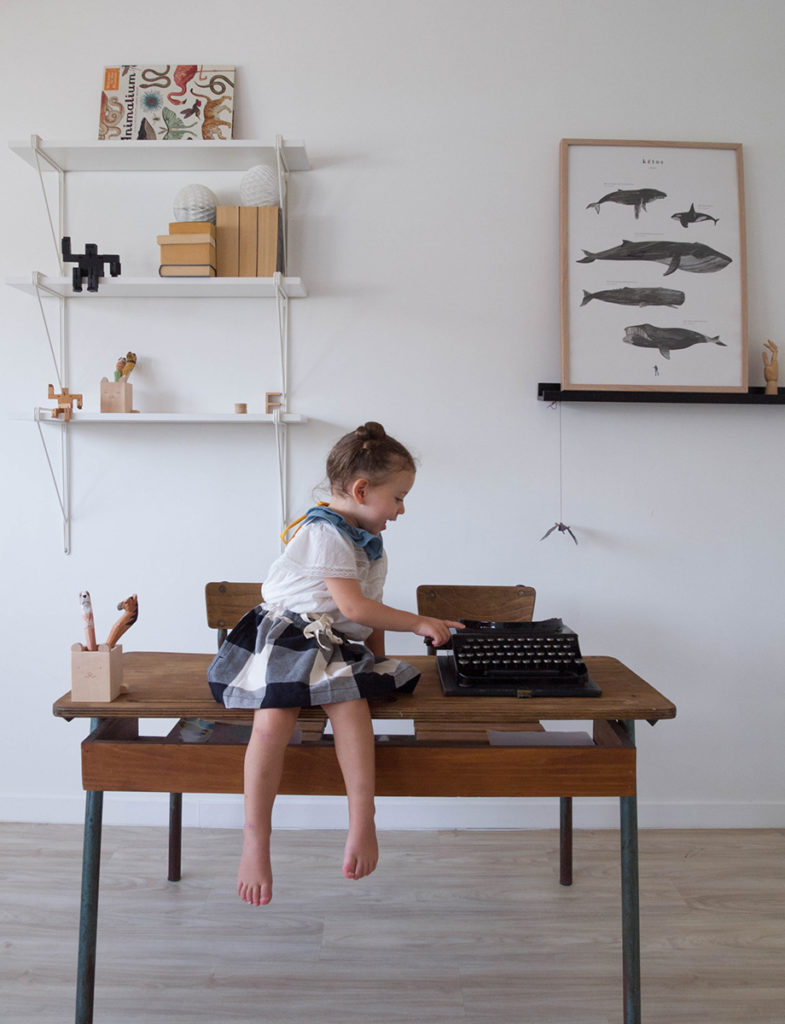 little girl sitting on a desk