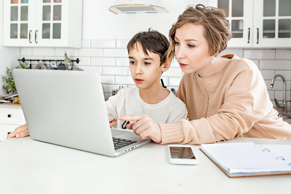 mother teaching son on a computer