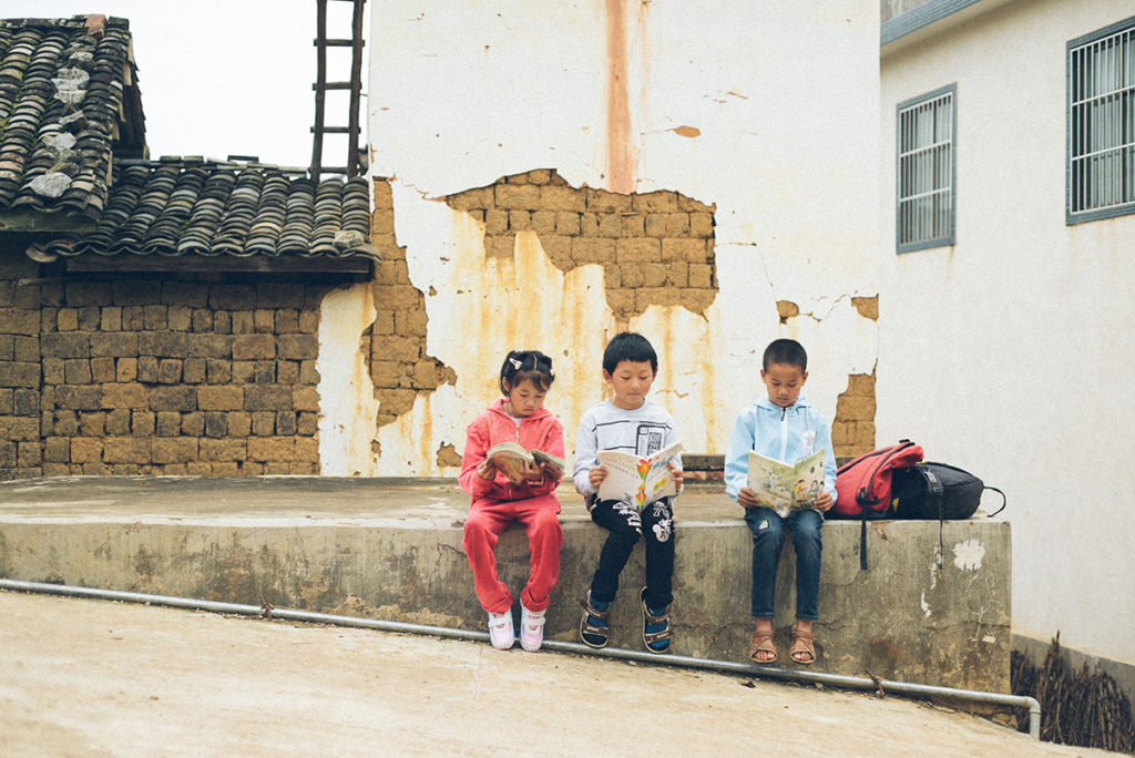 3 kids sitting on a wall