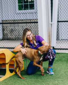 female employee playing with dog