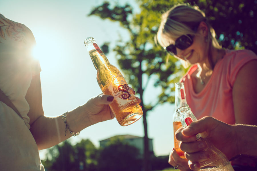 two females drinking beer in the sunshine