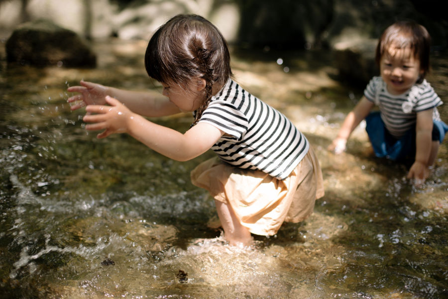 Two Asian girls playing in a stream