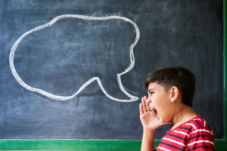 young boy yelling with talking bubble on chalkboard