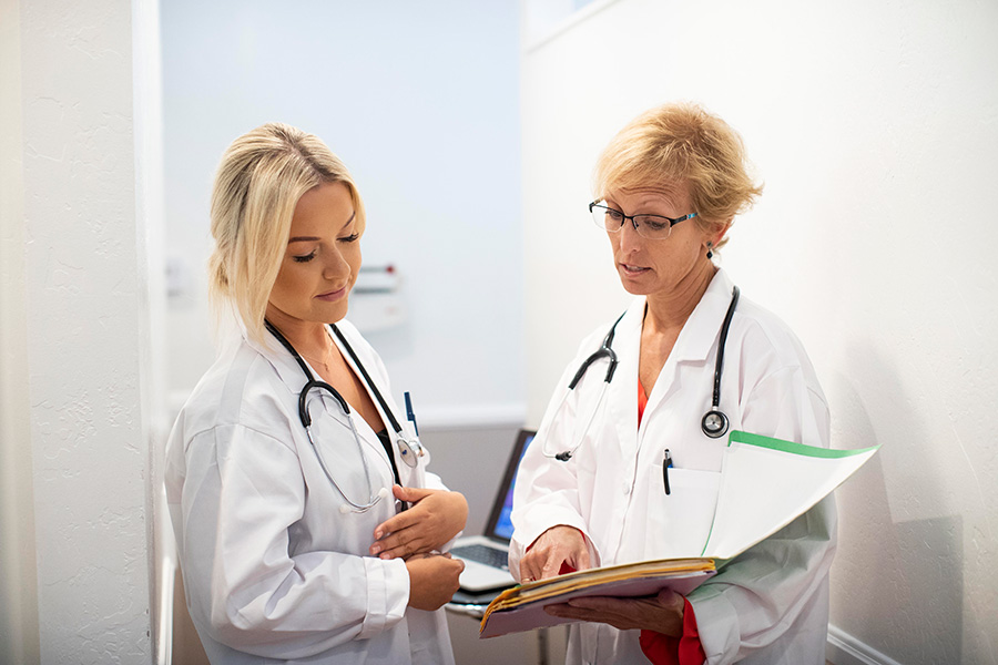 two female doctors looking at charts