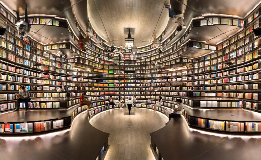 Library filled with books and lights with a reflective mirror on the ceiling