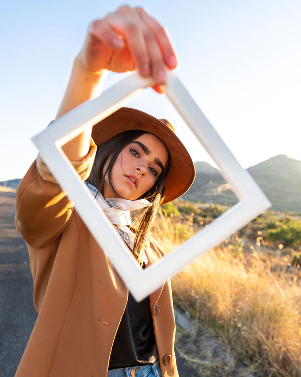 Close up of woman holding up a picture frame looking through it