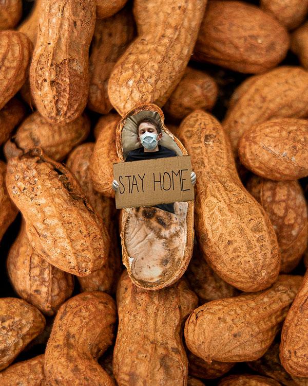 Man laying inside of a peanut with stay home sign wearing a mask and gloves