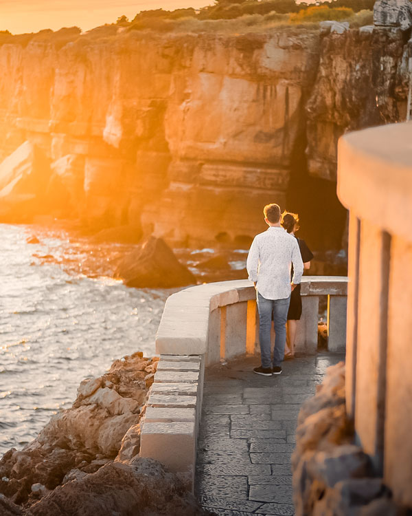 Couple on a balcony overlooking the waves and rocky cliffs