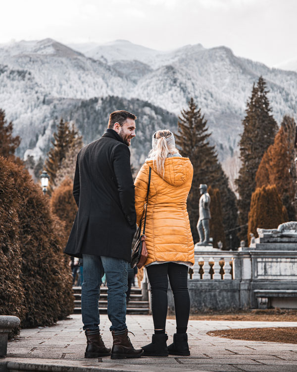 Couple with backs facing the camera but looking at the snowy mountains