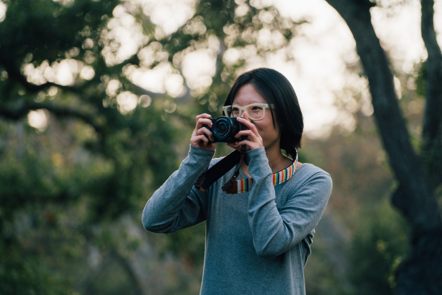 girl with glasses holding a camera up to her face