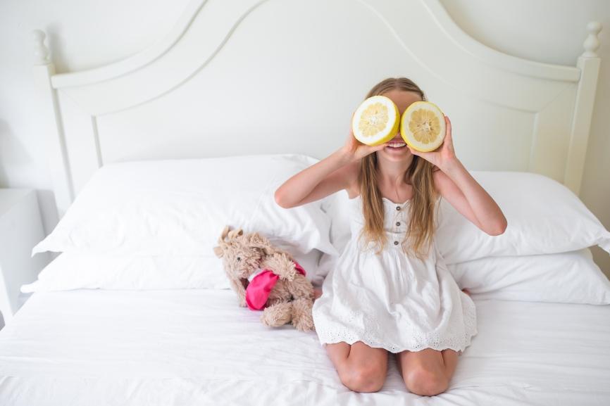Little girl covering eyes with citrus lemons posing in her room