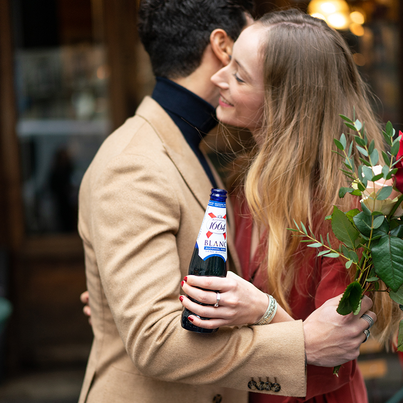man and woman hugging while the girl holds a bottle of kronenberg