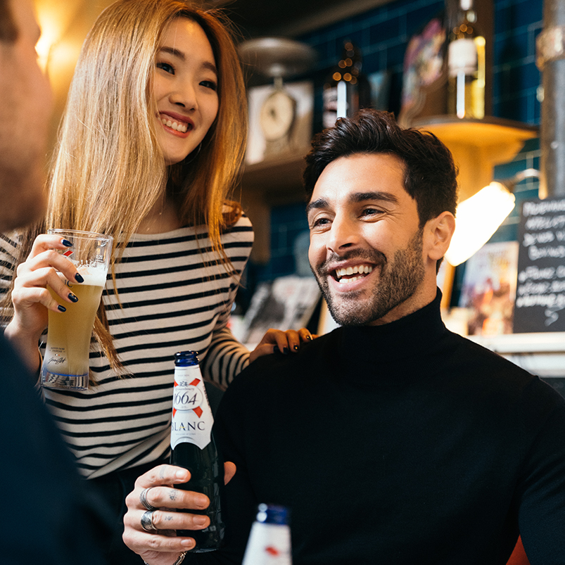 carlsberg guy and girl standing with a bottle and glass of kronenberg