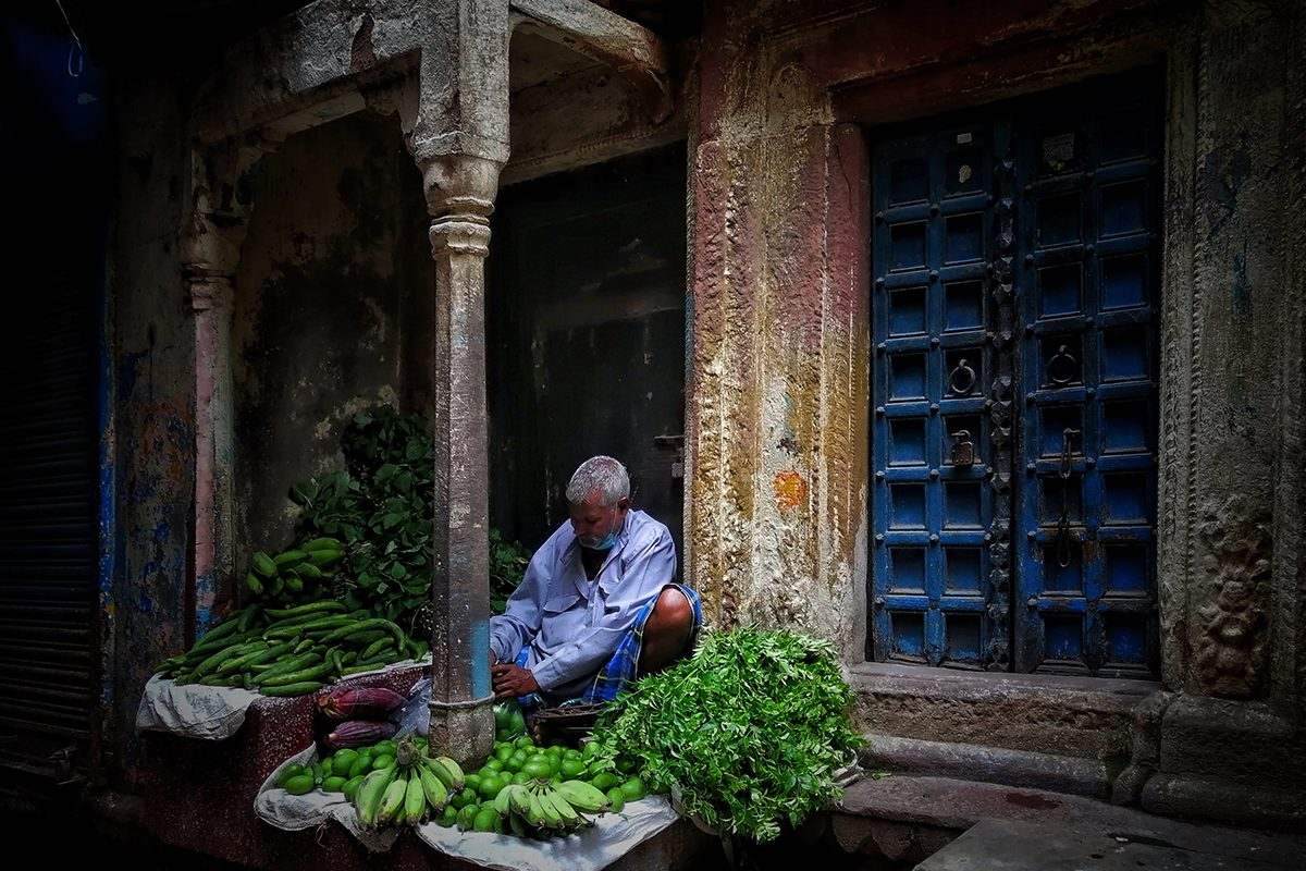 man sitting under an overhang laying out fruits and vegetables
