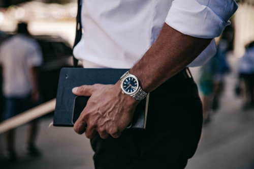 man holding phone and book with tag heuer watch on