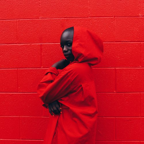 portrait girl in red hoodie in front of a red wall
