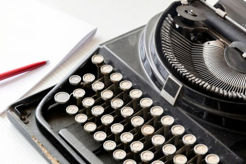 Close up of typewriter with pen and paper in the back