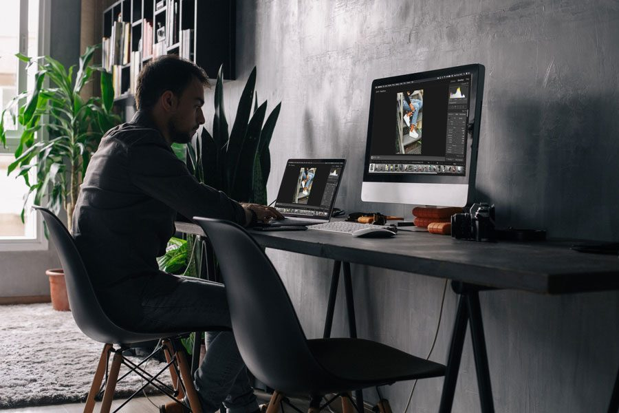Man working from home and sitting with computer in front of him.