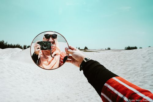 girl holding mirror and she is in the mirror holding a camera