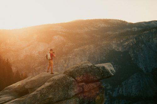 Photographer taking photo on rock cliff